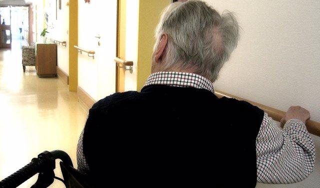 Archivo - Una persona en silla de ruedas se desplaza por los pasillos de una residencia de mayores.