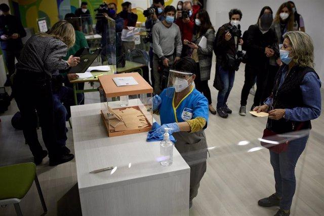 Una trabajadora de la limpieza desinfecta una mesa electoral en el colegio La Inmaculada-Marillac, a 4 de mayo de 2021, en Madrid (España).