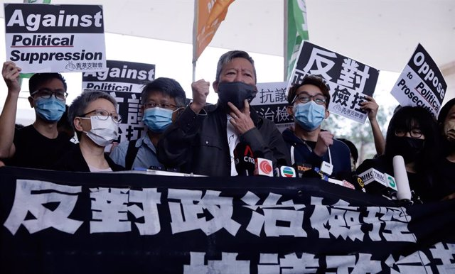 16 April 2021, China, Hongkong: Lee Cheuk-yan (C) and social activist Figo Chan (R) take part in a protest outside the West Kowloon Magistrates' Courts expressing their continuation of the struggle for freedom and democracy. A Hong Kong court on Friday se