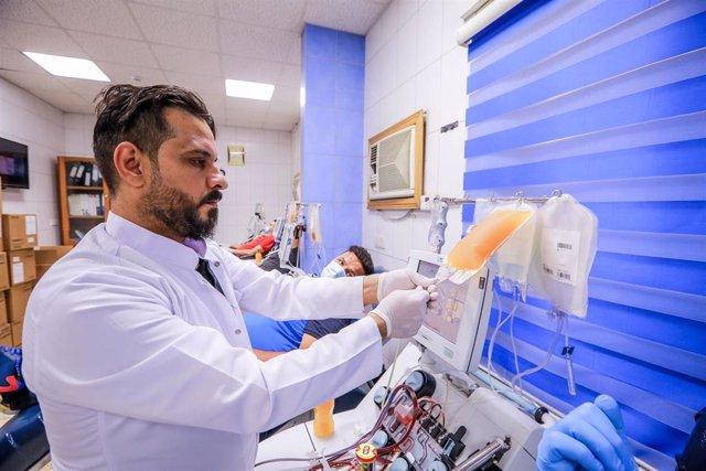 Archivo - Un trabajador médico en Irak con una donación de sangre de un paciente recuperado del coronavirus