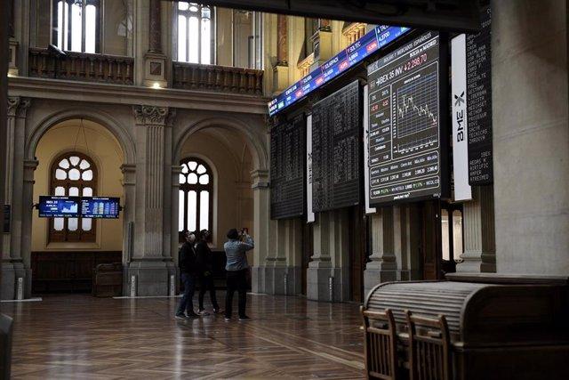 Un grupo de personas realiza una fotografía a los valores del Ibex 35 en el Palacio de la Bolsa, a 19 de abril de 2021, en Madrid, (España).