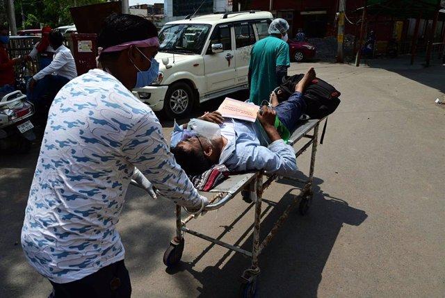 04 May 2021, India, Prayagraj: A medic transports a COVID-19 patient into the Swaroop Rani Neharu Hospital amid critical coronavirus infection rates. Photo: Prabhat Kumar Verma/ZUMA Wire/dpa