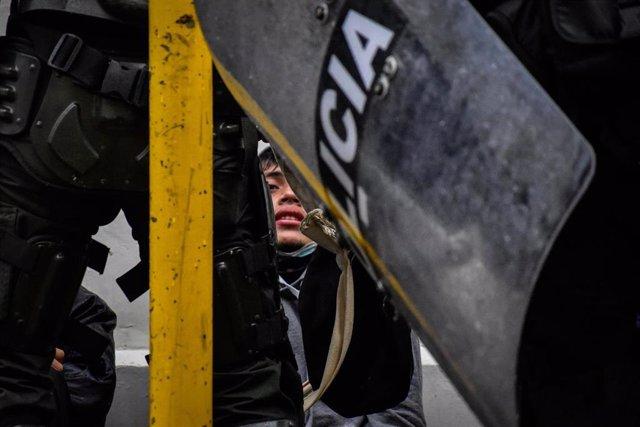 Un joven es detenido por un grupo de agentes del Escuadrón Móvil Antidisturbios (ESMAD) durante las últimas protestas en Colombia.