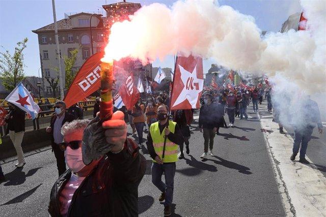 """Archivo - Decenas de personas con banderas de sindicatos y humo durante una manifestación convocada por varios sindicatos""""en defensa del empleo, por un futuro industrial, contra la represión sindical en Alu Ibérica"""" en la plaza de Ourense de A Coruña."""