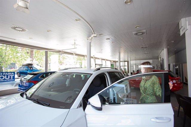 Archivo - Una trabajadora abre un coche aparcado en el interior de un concesionario de Vitoria-Gasteiz