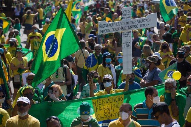 01 May 2021, Brazil, Rio de Janeiro: Supporters of Brazilian President Jair Bolsonaro hold flags during a protest near Copacabana beach, to mark the May Day, International Worker' Day. Photo: Fernando Souza/dpa
