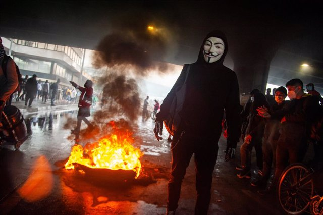 28 April 2021, Colombia, Bogota: Aprotester wearing a Guy Fawkes mask stands in front of burning tires during clashes at a protest against the government's tax reform bill. Photo: Chepa Beltran/LongVisual via ZUMA Wire/dpa