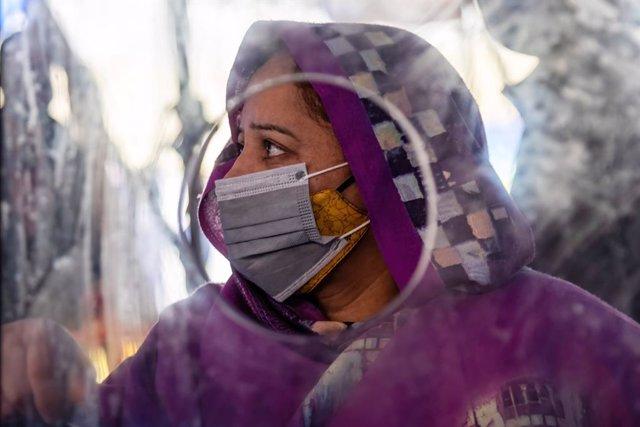 Una mujer espera para realizarse una prueba de coronavirus en India