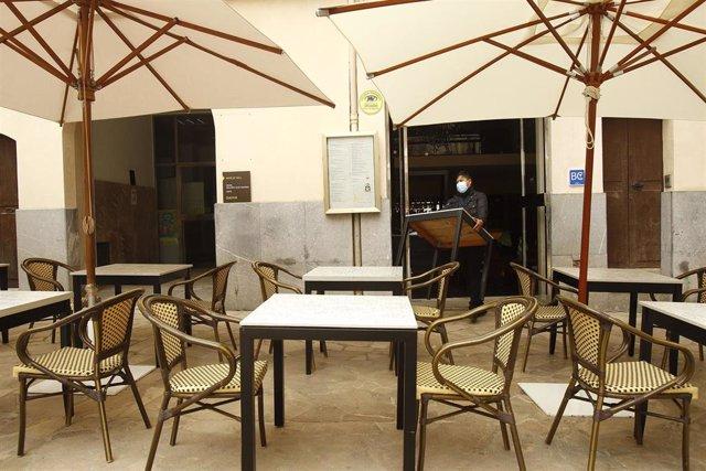Archivo - Un trabajador saca a la terraza de un bar mesas y sillas.