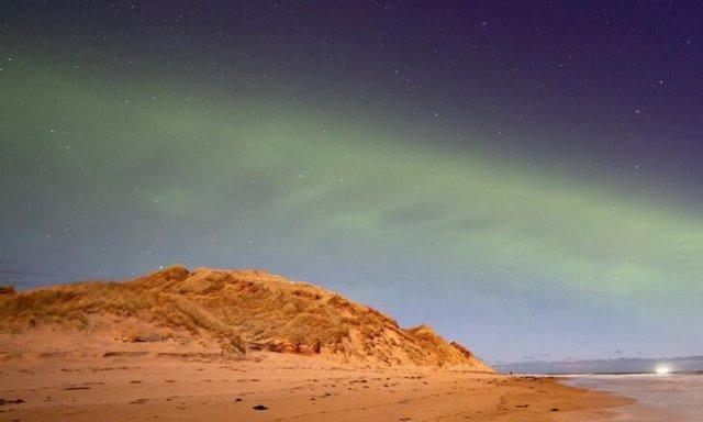 Un patrón de onda constante teñido de verde se puede ver en el evento de la aurora boreal similar a una duna.