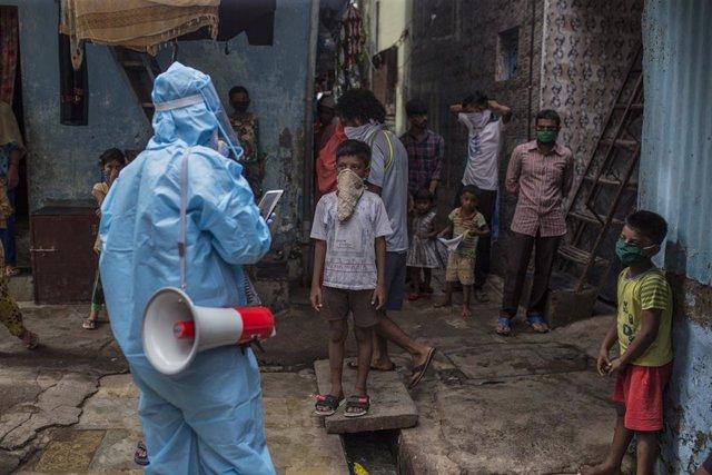 Archivo - Un trabjador sanitario da pautas a la población sobre cómo protegerse del coronavirus en India.