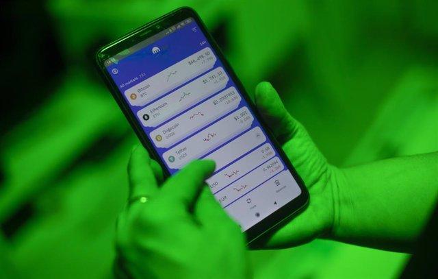 Archivo - Una internauta utiliza la aplicación Kraken para invertir en criptomonedas, en Madrid (España.