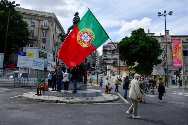 01 May 2021, Portugal, Lisbon: A man with a Portuguese flag marches near a monument in central Lisbon during a demonstration organized by the workers' unions, to mark the May Day, International Workers' Day. Photo: Jorge Castellanos/SOPA Images via ZUMA W