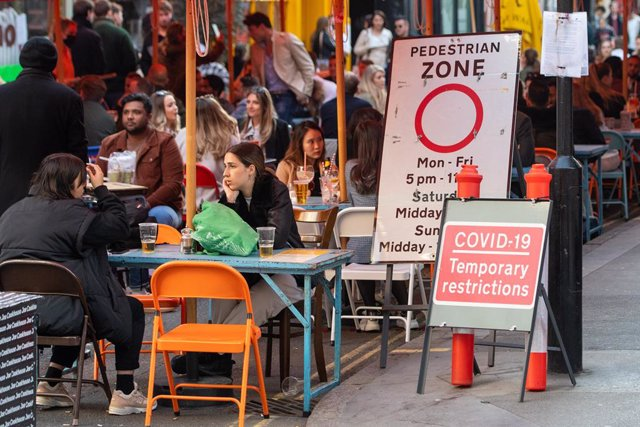 24 April 2021, United Kingdom, London: People are seen at an outdoor restaurant in Soho square following the further easing of lockdown restrictions in England. Photo: Dominic Lipinski/PA Wire/dpa
