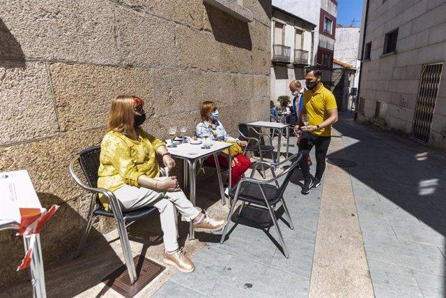 Dues dones en una terrassa en el municipi d'O Grove durant el primer cap de setmana d'obertura del tancament perimetral i l'hostaleria, a 2 de maig de 2021, a Pontevedra, Galícia (Espanya). O Grove va abandonar el nivell màxim de restriccions el passat vi