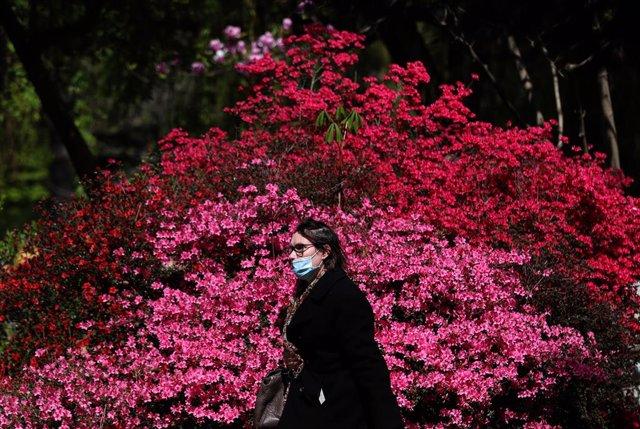 Una mujer ataviada con mascarilla camina por París.