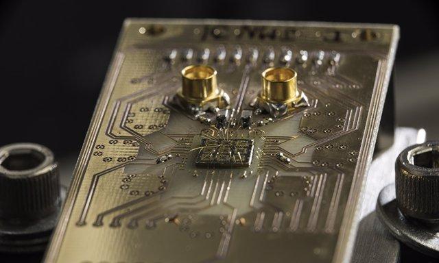 Archivo - Se muestra un chip semiconductor de procesador cuántico conectado a una placa de circuito.