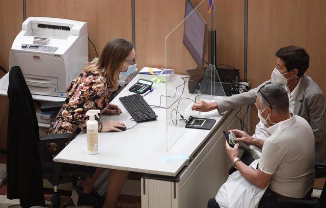 Archivo - Una trabajadora de una oficina de la Agencia Tributaria en Madrid atiende a dos contribuyentes.