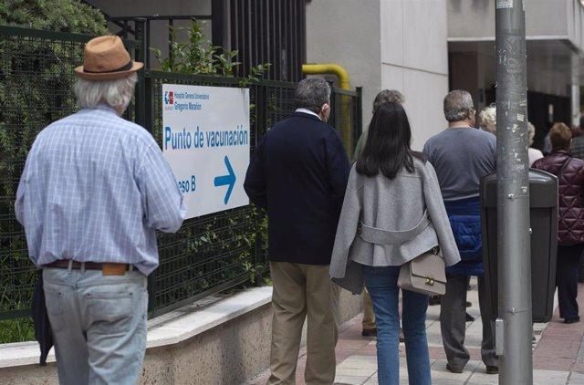 Varias personas esperan para recibir la vacuna contra el Covid-19, a 27 de abril de 2021, en el Hospital Gregorio Marañón, Madrid, (España). A este centro hospitalario, que lleva desde el pasado 10 de abril inoculando la vacuna de Pfizer contra el Covid-1