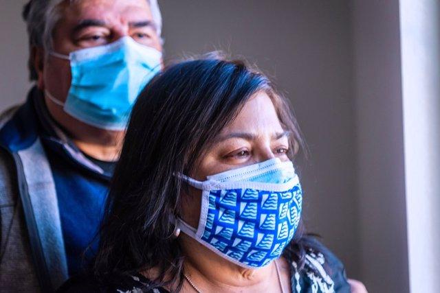 Archivo - Pareja madura con una máscara protectora mirando a través de la ventana. Obesidad. Coronavirus. Covid.