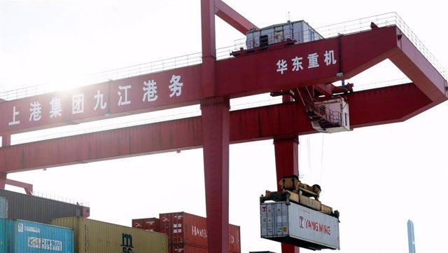Archivo - Imagen de una grupo portando un contenedor en un puerto en China.