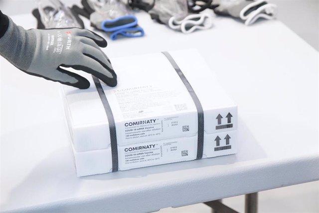 Un trabajador saca de una caja el envío de vacunas de Pfizer/BioNTech contra el Covid-19