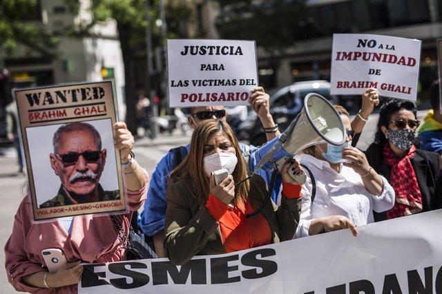 Una mujer con un megáfono, acompañada de varias personas con carteles, protestan contra el líder del Frente Polisario en la puerta de la Audiencia Nacional, a 7 de mayo de 2021, en Madrid, (España). Esta es una de las protestas organizadas contra Brahim G
