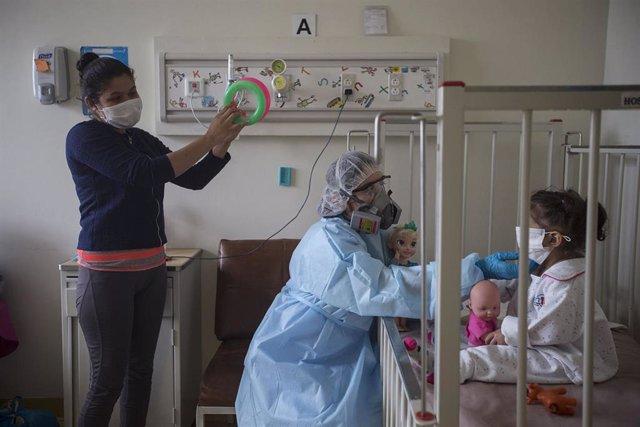 Archivo - Una mujer y una enfermera entretienen a una niña con coronavirus en el Hospital Infantil San Borja, en Lima.