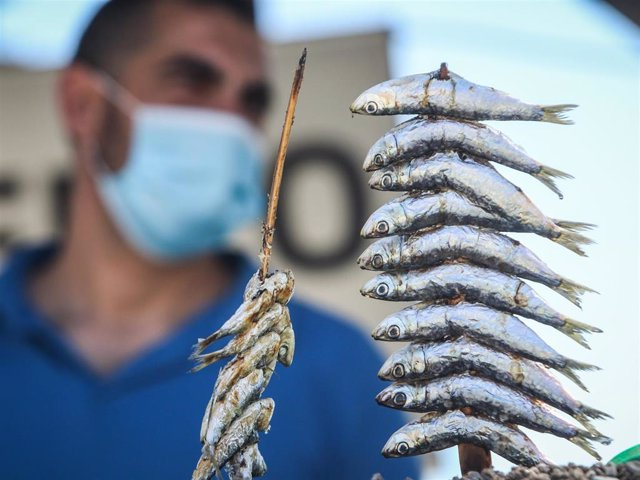 On the beach of Pedregalejo man prepares thickets of sardines with mask and safety measures due to the coronavirus crisis