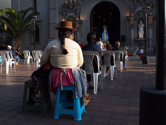Una mujer en un acto religioso adaptado a las medidas contra la COVID-19 en Lima.
