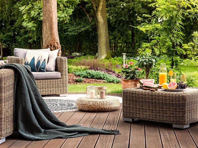 Close-up of rattan table with fruit and juice on it standing on a wooden patio in a spa facility garden