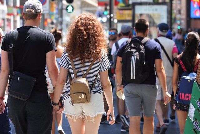 Archivo - Una pareja cruza de la mano un paso de peatones