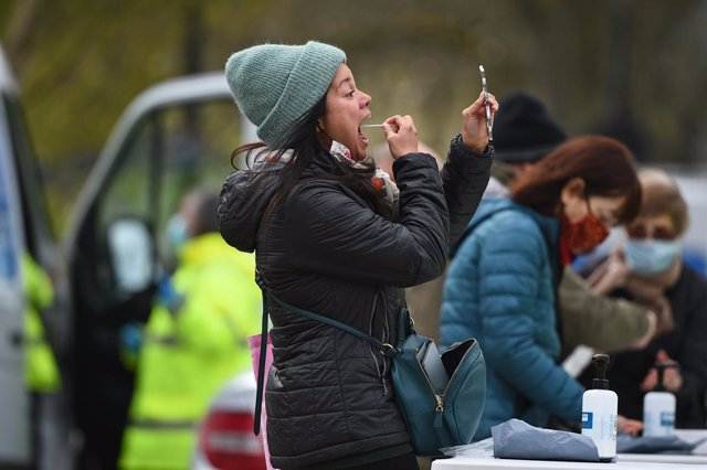 13 April 2021, United Kingdom, London: A lgirl takes a nasal swab herself during a coronavirus surge testing on Clapham Common. Thousands of residents have queued up to take coronavirus tests at additional facilities set up after new cases of the South Af