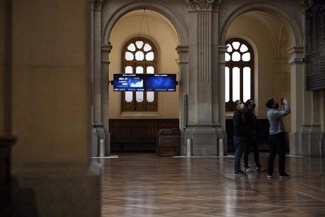Un grupo de personas realiza una fotografía a los valores del Ibex 35 en el Palacio de la Bolsa