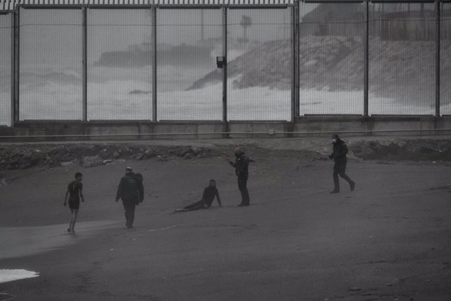 Dos jóvenes migrantes marroquíes han llegado a la playa del Tarajal después de salir a nado desde la ciudad marroquí de Castillejos, a 24 de abril de 2021, en Ceuta.