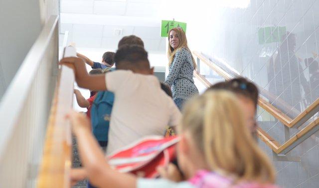 Niños de Primaria se dirigen a su aula junto a una trabajadora del centro escolar