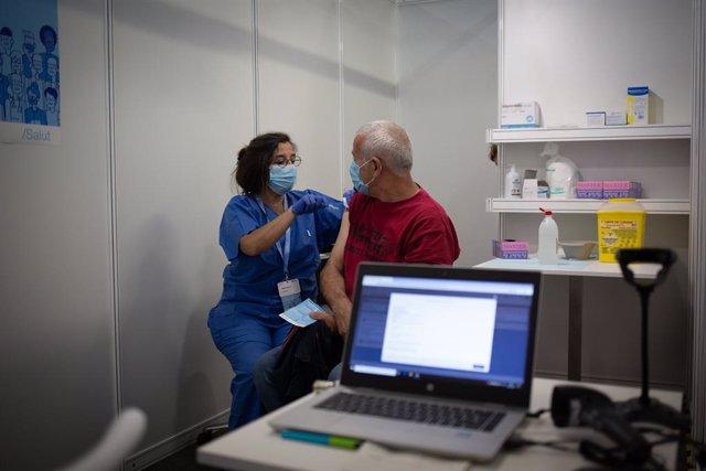 Arxiu - Una sanitària vacuna un home en el circuit de vacunació de Fira de Barcelona.