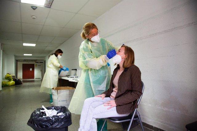 Archivo - Una sanitaria realiza un test de antígenos o una PCR a una mujer.