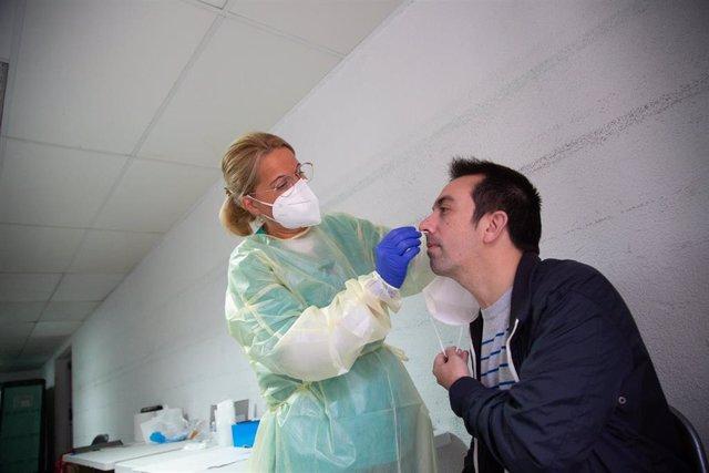 Archivo - Una sanitaria realiza un test de antígenos o una PCR a un hombre.