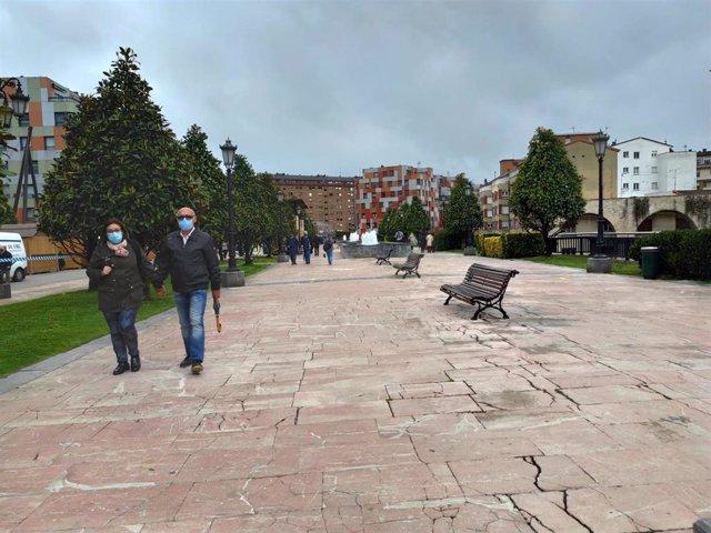 Personas paseando por La Losa de Oviedo en un día de primavera, con mascarillas.