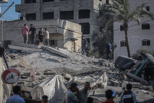 """14 May 2021, Palestinian Territories, Gaza City: Palestinians inspect the remains of the """"Production Bank"""", an institution linked to the Palestinian Islamist movement Hamas, after it was hit by Israeli airstrikes, amid the escalating flare-up of Israeli-P"""