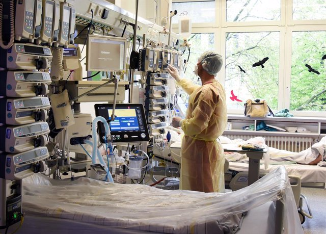 12 May 2021, Saxony-Anhalt, Halle: A specialist nurse for anaesthesia and intensive care, checks an infusion and syringe pump tower at a patient's bedside next to an empty bed in the interdisciplinary intensive care unit in the Coronavirus (Covid-19) area