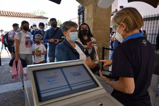 Persones fan cua per entrar al parc d'atraccions PortAventura en dia de la seva reobertura