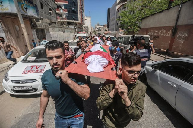15 May 2021, Palestinian Territories, Gaza City: Palestinians carry the bodies of the Abu Hatab family during their funeral in Gaza City. Eight children and two women, all belonging to the Abu Hatab family, were killed in the three-storey building in Shat