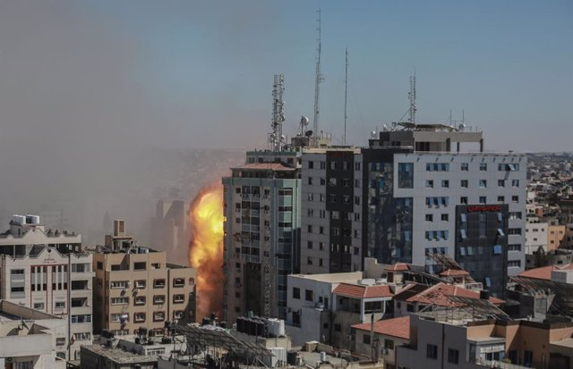 15 May 2021, Palestinian Territories, Gaza City: Smoke and flames rise after an Israeli air-strike hits at Al-Jalaa tower, which houses apartments and several media outlets, including The Associated Press and Al Jazeera, amid the escalating flare-up of Is