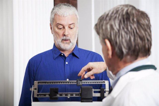 Archivo - Hombre pesándose en una báscula en la consulta del médico.