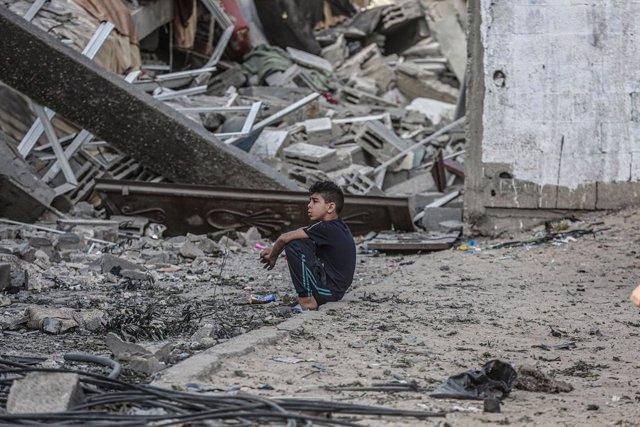 Un xiquet palestí assegut sobre les runes d'uns edificis afonats pels atacs aeris de les forces israelianes.