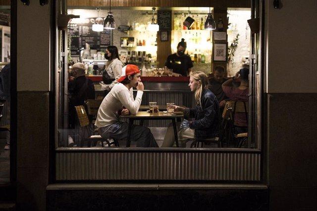 Dos jóvenes en el interior de un bar en el barrio de las Letras, zona típica de tapas y copas de la capital, a 14 de mayo de 2021, en Madrid (España). Madrid ha reforzado el dispositivo de la Policía Municipal para este San Isidro, apoyo que ha arrancado