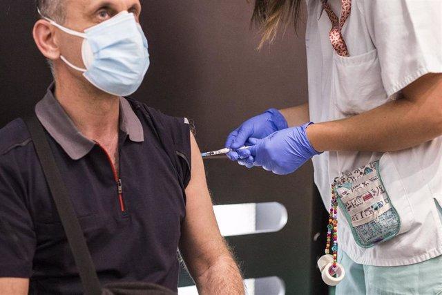 Una sanitaria administra la primera dosis de la vacuna de Pfizer a un hombre, en el Hospital Universitario de Getafe, a 17 de mayo, en Getafe, Madrid (España). La Comunidad de Madrid ha comenzado hoy a vacunar a personas entre 50 y 55 años en los hospital