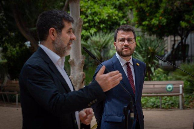 El secretari general de Junts, Jordi Sànchez (i) i el president de la Generalitat en funcions, Pere Aragonès (d) durant una roda de premsa en els jardins del Palau Robert